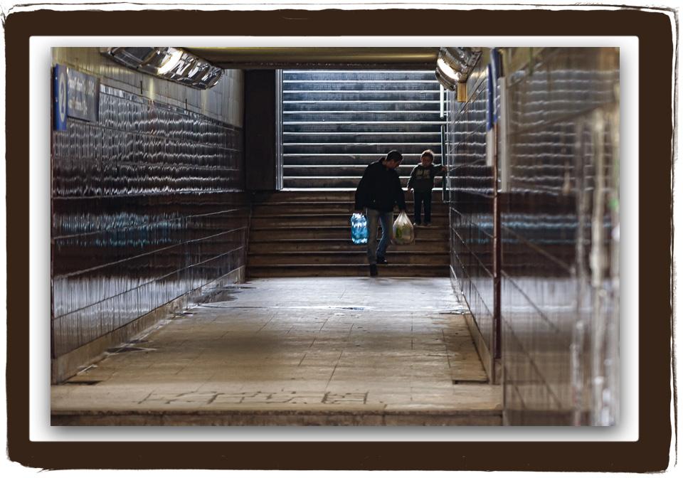 Padre e figlio scendono dalle scale alla stazione